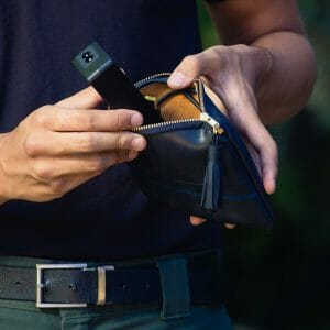 Close up man pulling charger out of black maudernise pouch
