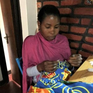 woman in pink shawl sewing