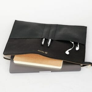 open organizer with pens and headphones and laptop and book